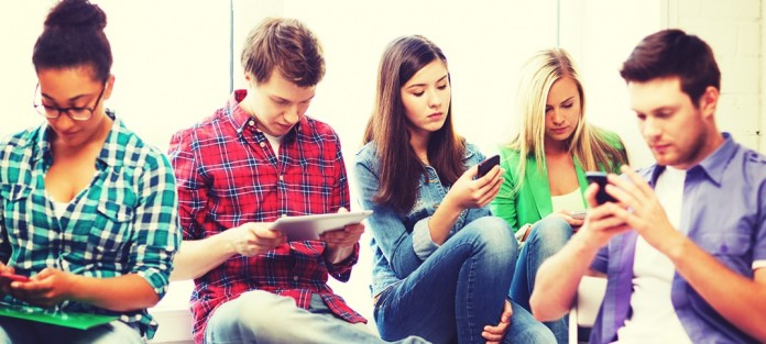 group of teenagers using mobile phone