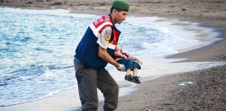 Aylan Kurdi carried by a policeman
