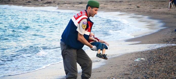 Aylan Kurdi carried by a policeman